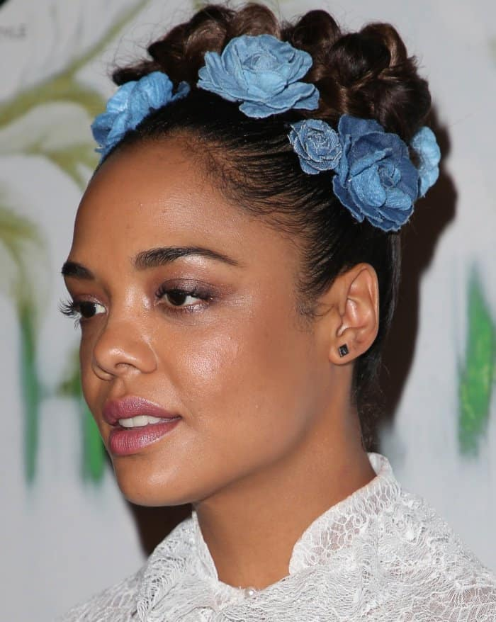 "Tessa Thompson wearing a crown of blue flowers nestled on top of her braided updo at the ""Woodshock"" premiere"