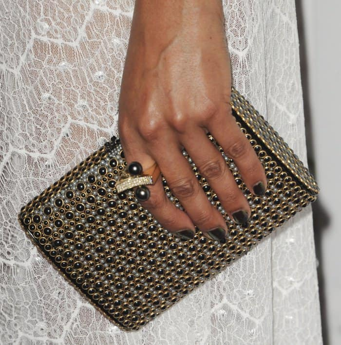 "Tessa Thompson carrying an embellished black-and-gold clutch at the ""Woodshock"" premiere"