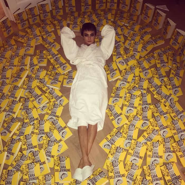 """Cara Delevingne """"swims"""" in her books inside her London hotel"""