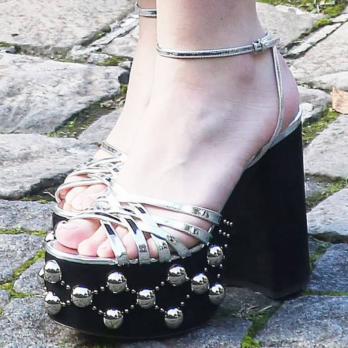 "Dakota pulled off the iconic Miu Miu quirk with a pair of ""Plateau"" studded platform sandals"