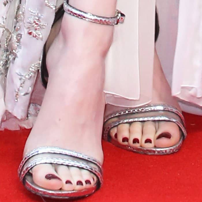 Emma wears a pair of silver ankle strap sandals