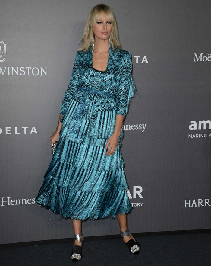 Karolina's design featured a blue-and-black patterned jacket and a fringed skirt, which she styled with tousled waves, Sharra Pagano statement earrings and an embellished clutch