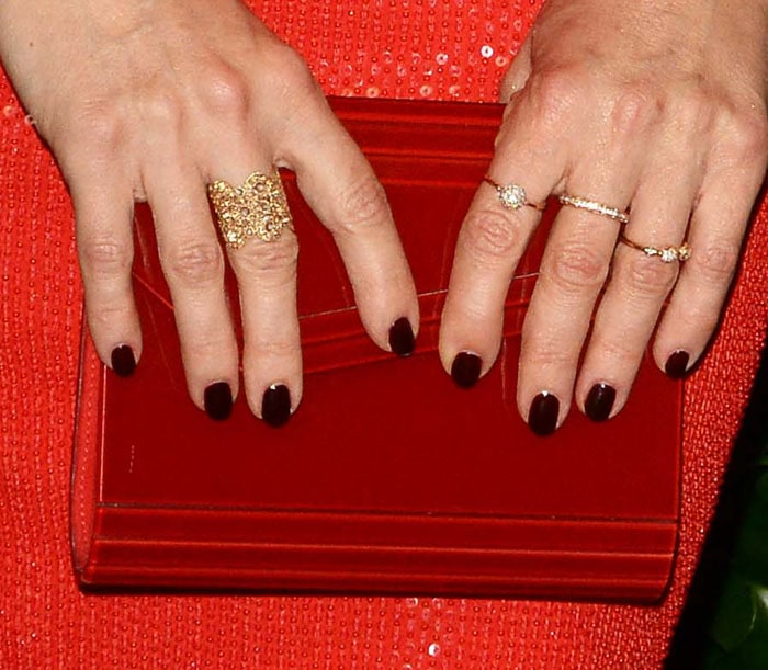 "The actress goes for a deeper red with a Jimmy Choo ""Candy"" clutch"