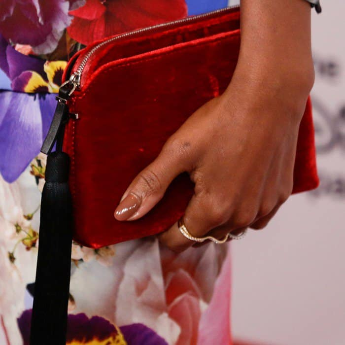 Kerry Washington toting The Row's crimson velvet wristlet clutch that is finished with a long black tassel
