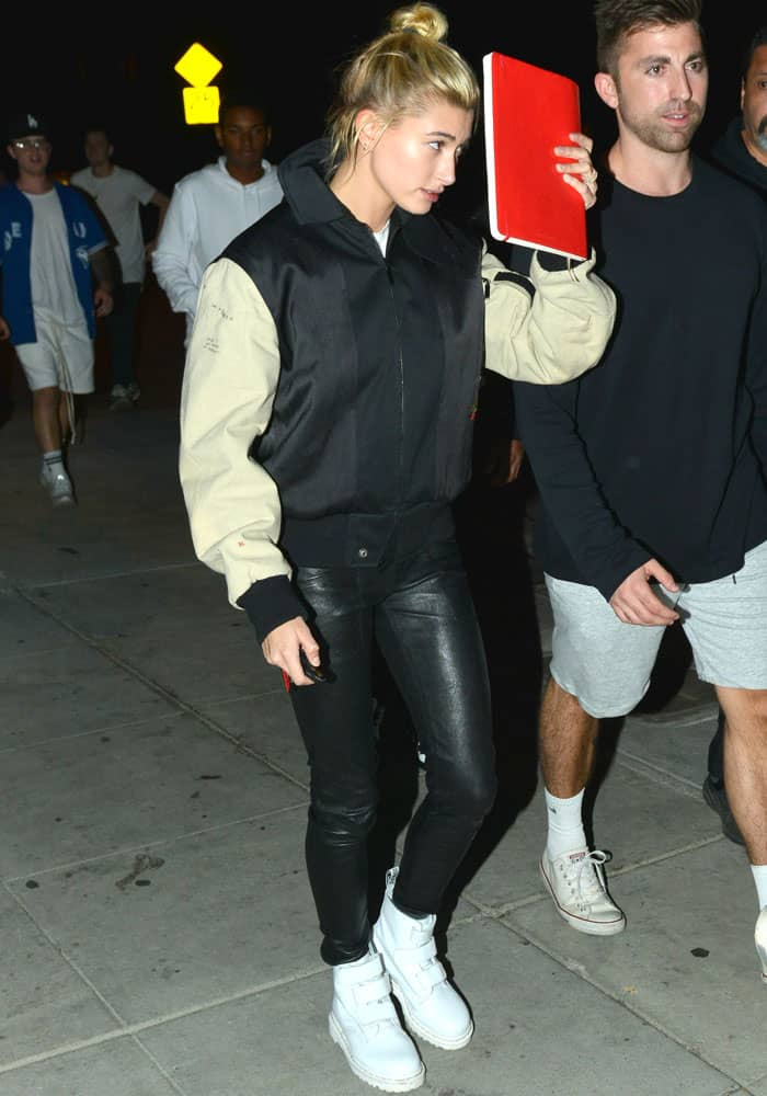 Hailey Baldwin covers her face as she heads to her car
