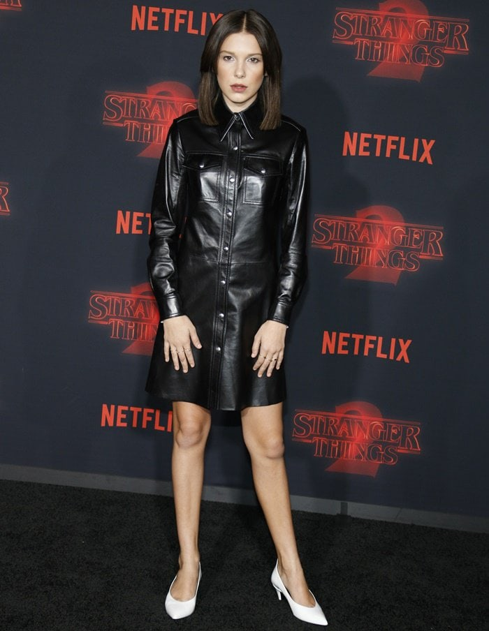 Millie Bobby Brown wearing a black leather shirt dress by Calvin Klein 205W39NYC at the season two premiere of 'Stranger Things' at the Regency Bruin Theatre in Westwood, California, on October 26, 2017
