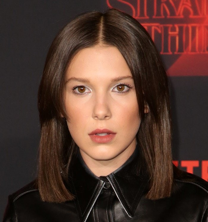 Millie Bobby Brown with shoulder-length straight hair parted down the middle