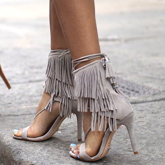 Fierce fringe tiers lend boho-chic style to an on-trend lace-up sandal set on a slim heel.