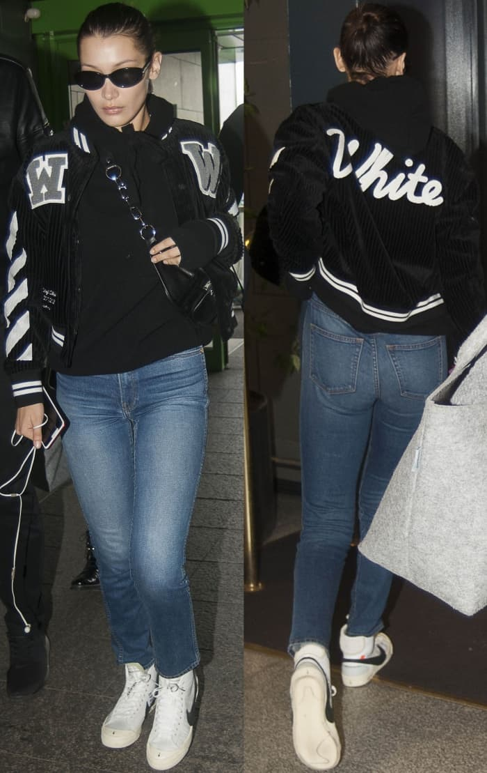 "Bella Hadid wearing an Off-White c/o Virgil Abloh cotton corduroy crop varsity jacket, denim jeans, and Off-White for Nike ""Blazer Mid"" sneakers at the Milan-Malpensa Airport"