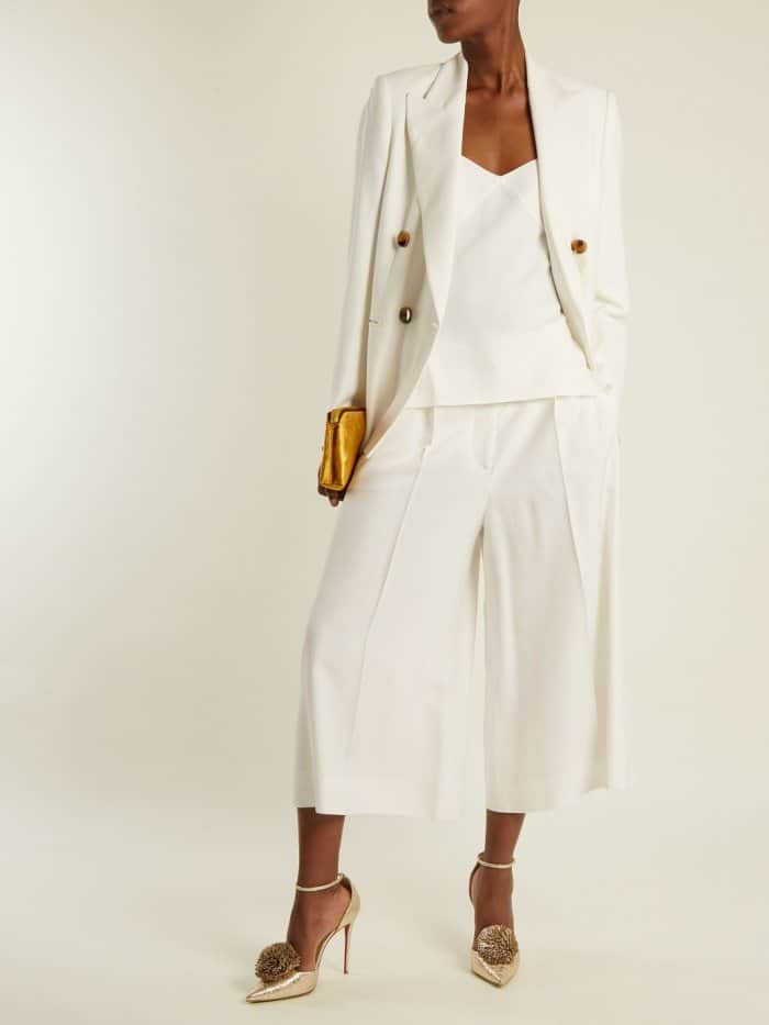 """Model wearing the Christian Louboutin """"Tsarou"""" pumps with the Khaite """"Isa"""" jacket, The Row silk cami top, and Stella McCartney """"Olivier"""" cropped trousers"""