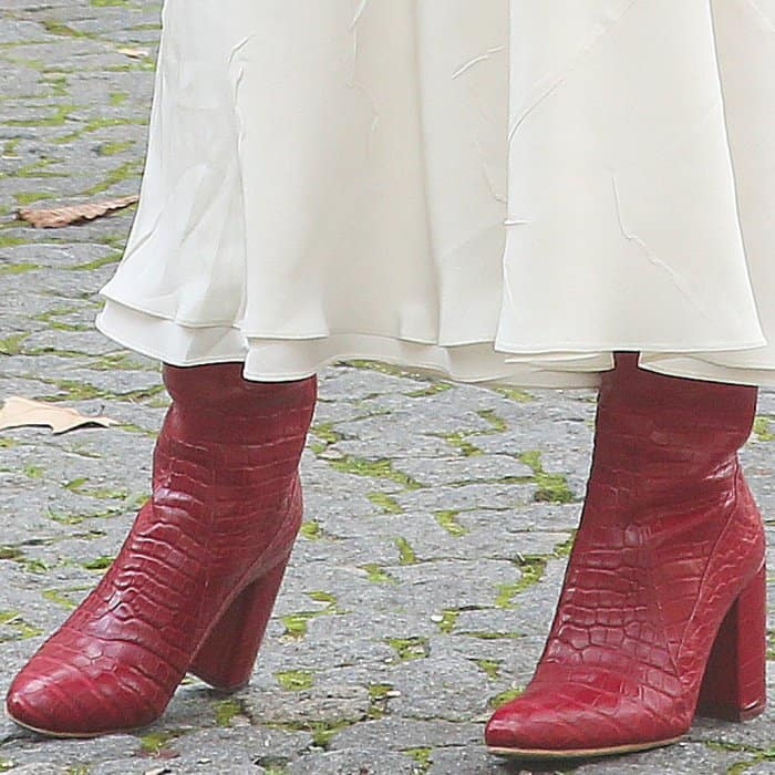 Emily Ratajkowski wearing Esquivel x Brock Collection red handstained alligator boots at the Miu Miu Spring/Summer 2018 fashion show during Paris Fashion Week