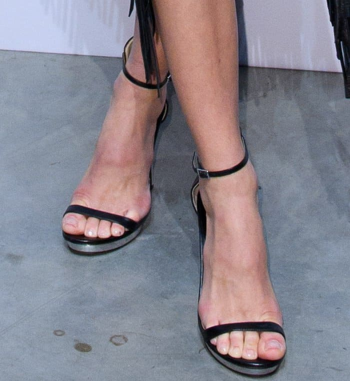 """Martha Hunt wearing the Michael Kors Collection """"Doris"""" sandals at the Michael Kors """"Sexy Ruby"""" fragrance launch in London"""