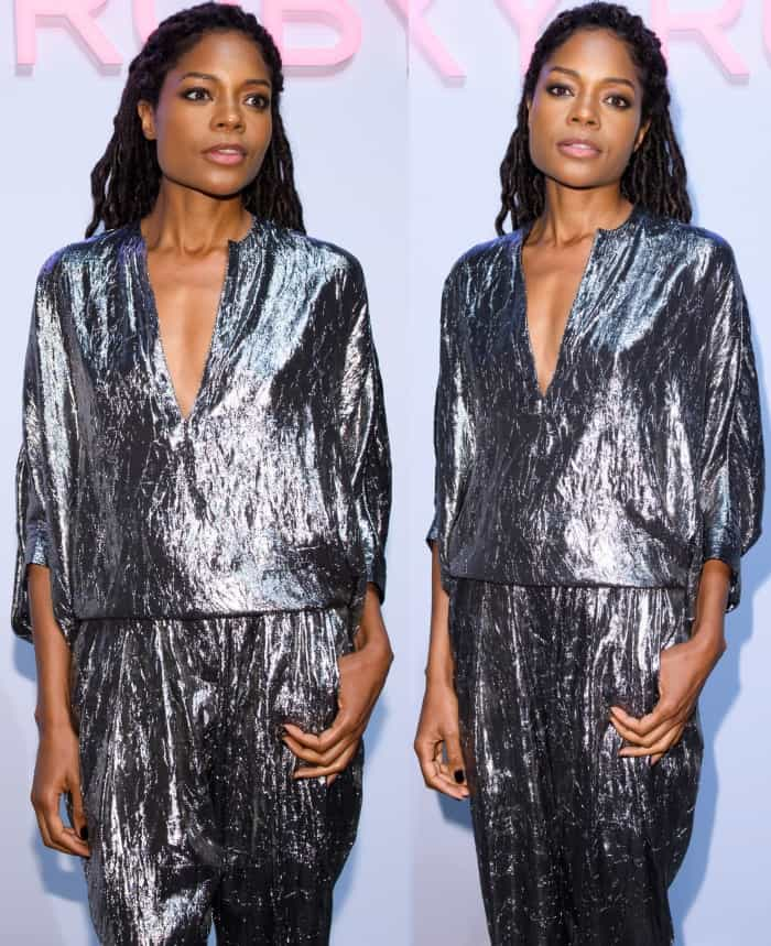 """Naomie Harris wearing a Michael Kors Collection crushed silver silk-blend lamé blouse and matching tapered pants with silver pointy-toe pumps at the Michael Kors """"Sexy Ruby"""" fragrance launch in London"""