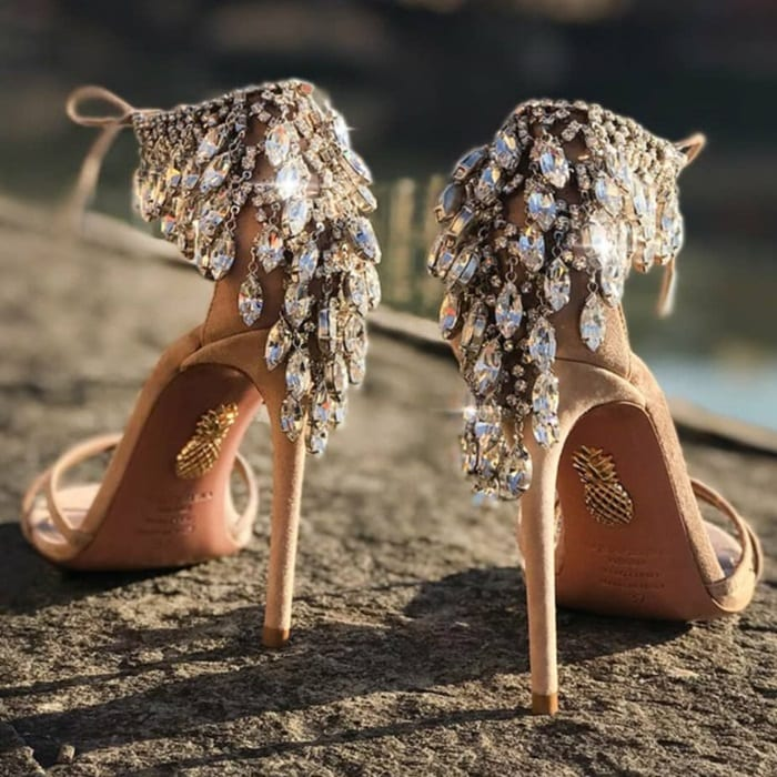 These beige suede ankle-tie sandals are embellished at the heel counter with dangling crystals in a silvertone setting