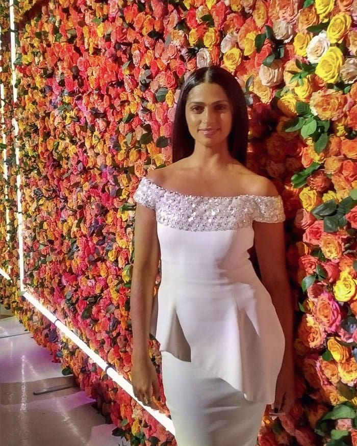 The beauty in white couldn't help but pose against a flower wall