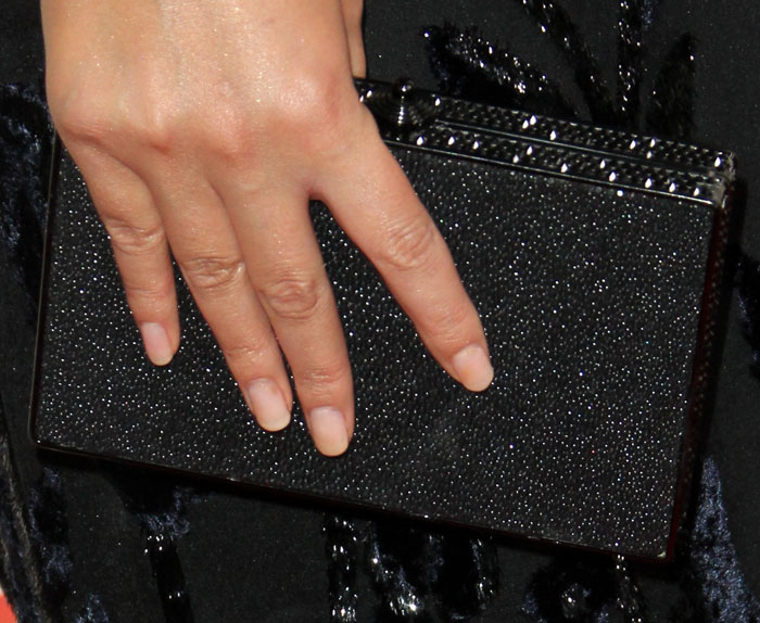 Chrissy adds more sparkle to her look with a glitter clutch