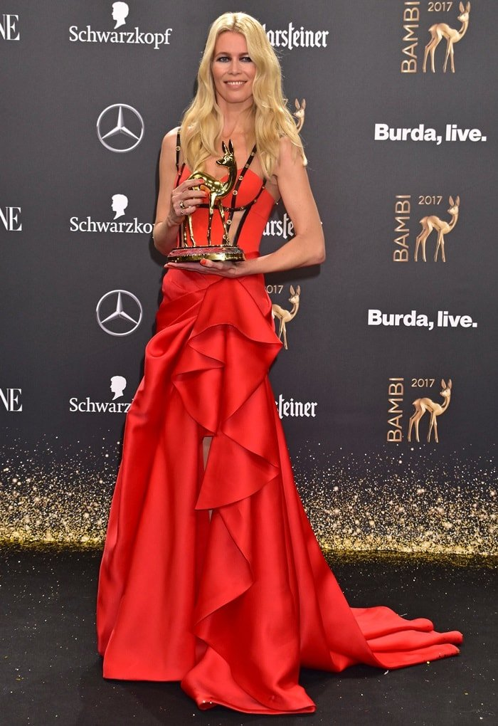 Claudia Schiffer wearing a custom-made Versace gown featuring corset panelling and gold Medusa studs