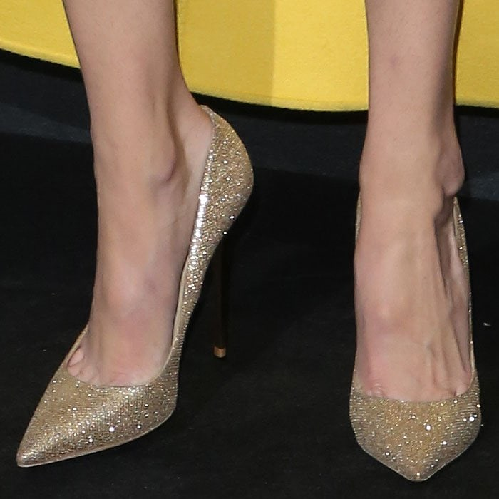 "Gigi Hadid wearing Jimmy Choo ""Anouk"" pumps in gold glitter lamé fabric."