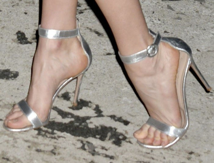 "The model gives the costume a slight update with a pair of silver Gianvito Rossi ""Portofino"" sandals"