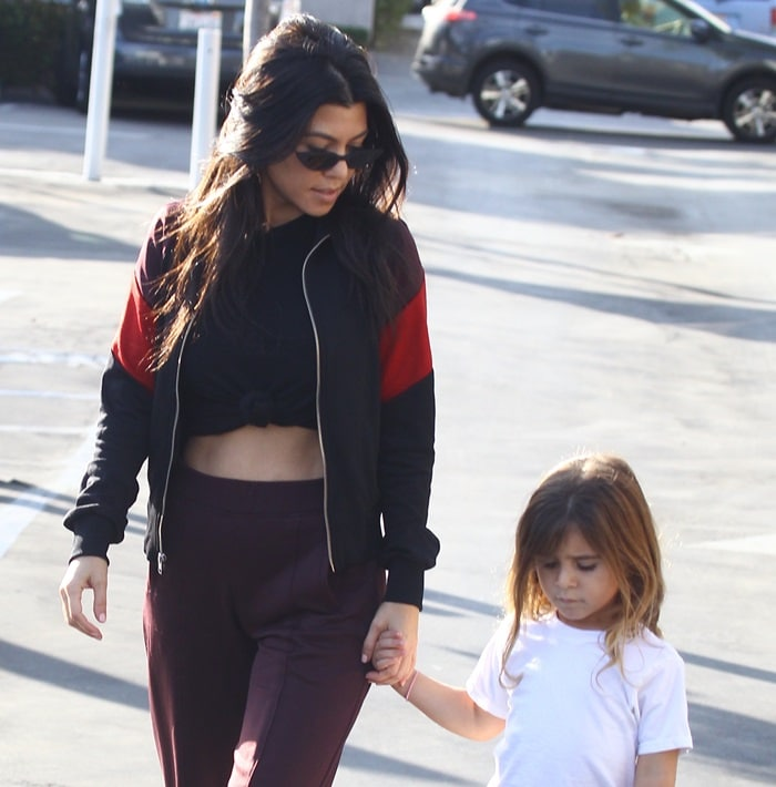 Kourtney flashed her impressive abs in a knot front t-shirt paired with high-waisted dark maroon pants
