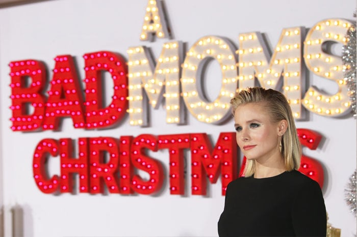 """Kristen poses beside the promos signage for """"A Bad Moms Christmas"""""""