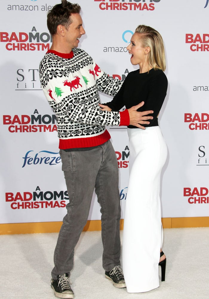 Kirsten's husband Dax Shepard surprises her on the carpet in a Christmas sweater