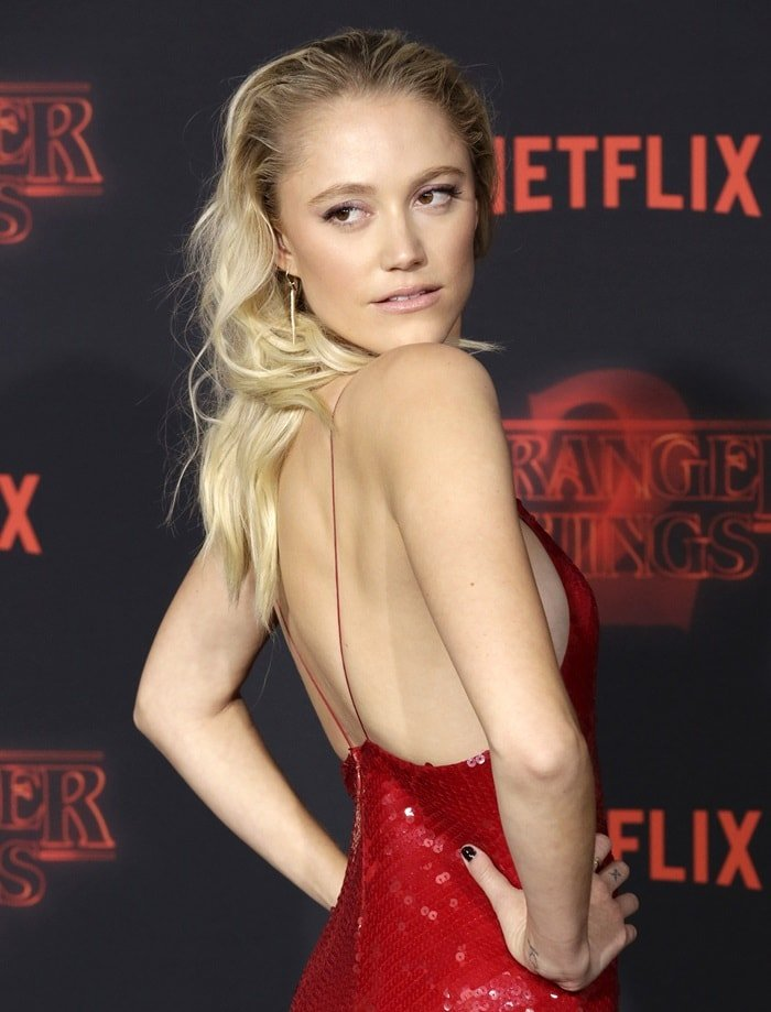Maika Monroe showing off her sexy back in a slinky red dress from Stella McCartney