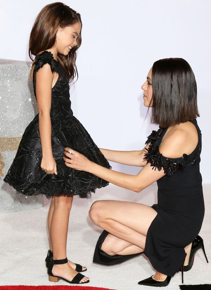 Mila fixes child actress Ariana Greenblatt's dress on the carpet