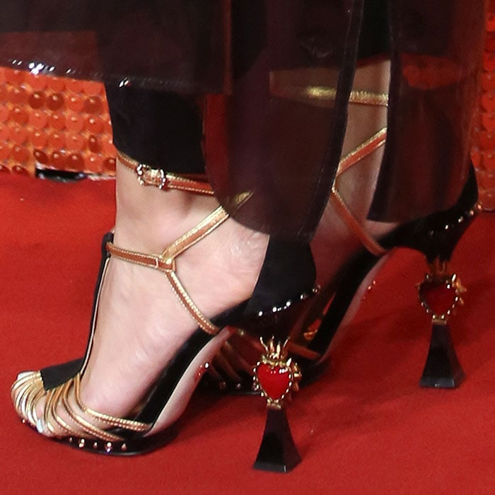 Closeup of the heart-detail heels on Pixie Lott's Dolce & Gabbana gold-and-black t-strap sandals.