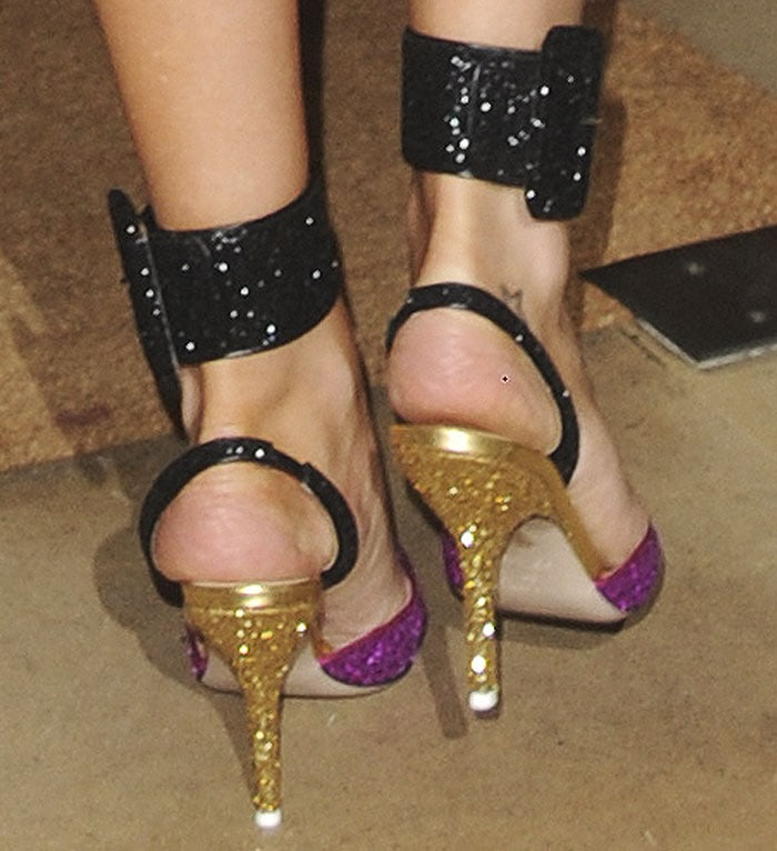 """The model wears the Attico """"Diletta"""" pumps with the brand's removable ankle straps"""