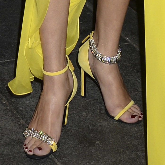 Selena Gomez shows off her feet in yellow Calvin Klein Camelle sandals with mismatched jeweled straps