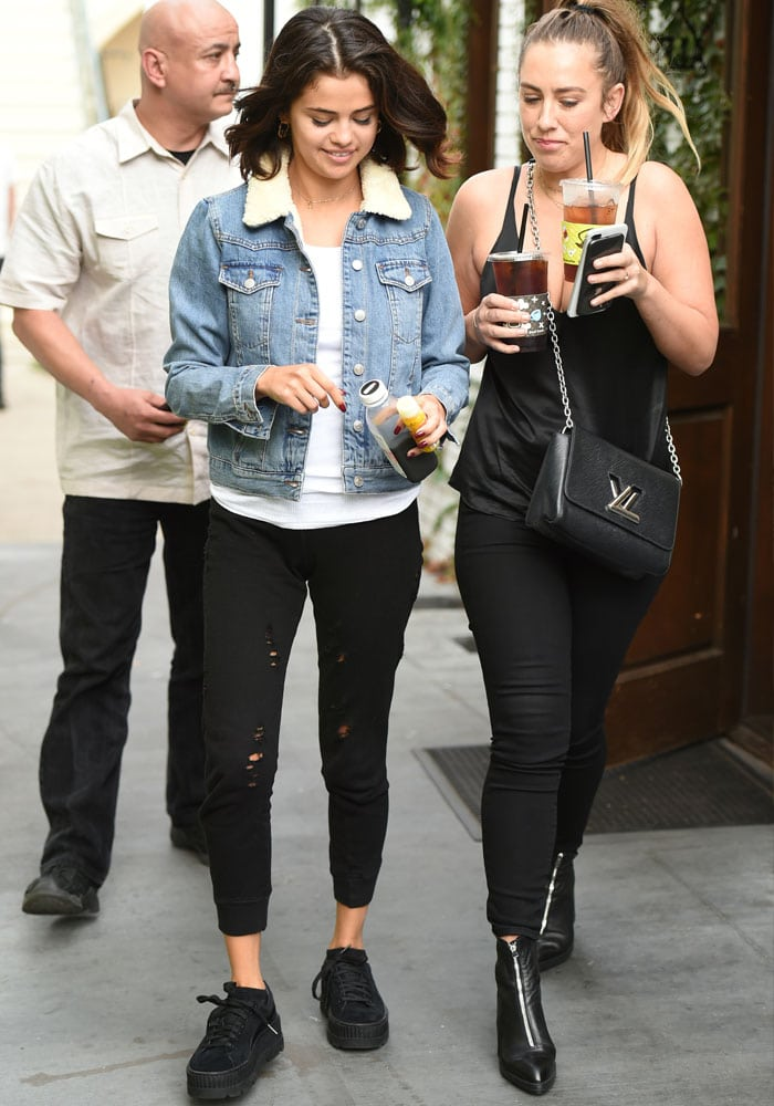 Selena emerges from the coffee shop with a friend