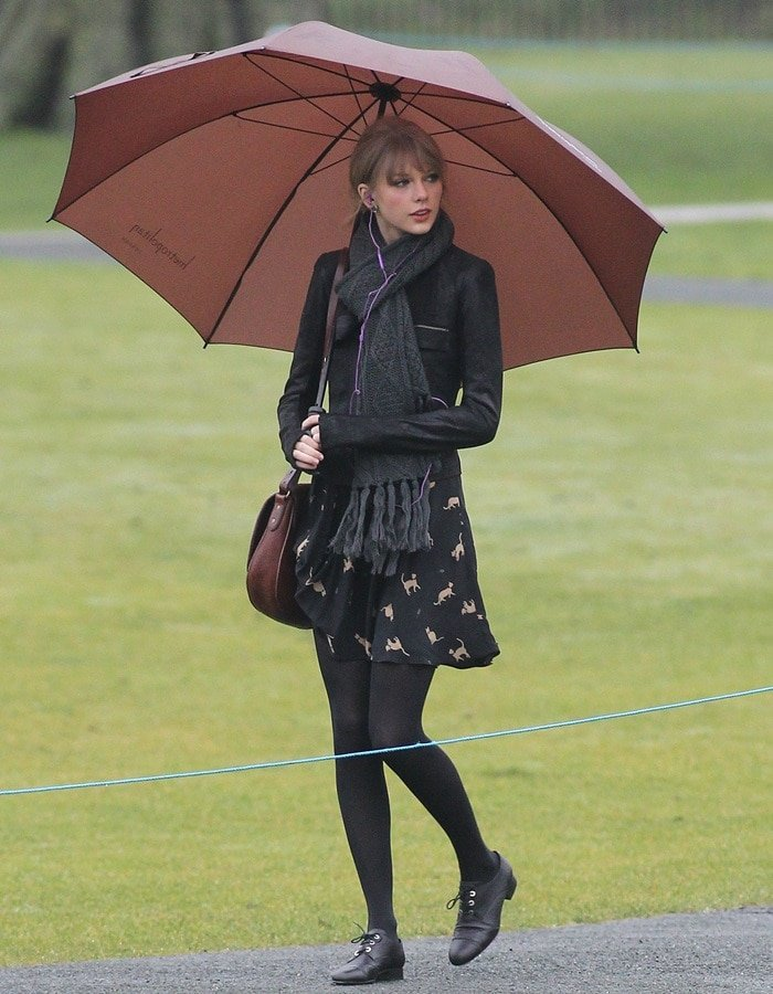 Taylor Swift's ensemble consisted of a Rick Owens jacket, a dress from ASOS with cat print, black leggings, matching patent leather Chanel oxfords with round toes, a huge brown umbrella, Skullcandy headphones, and a brown 'Rugby' pony hair saddle bag from Ralph Lauren.