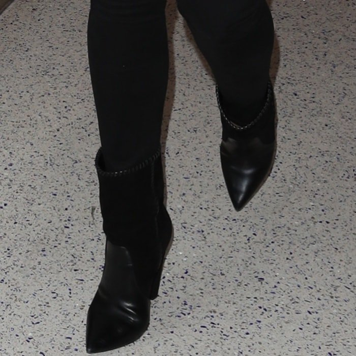 "Chrissy Teigen wearing Saint Laurent ""Niki"" mid-calf boots at the Los Angeles International Airport"
