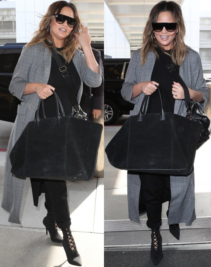 Chrissy Teigen wearing Yeezy Season 5 knit sock boots with a black top, black pants, and an Alice + Olivia coat at the Los Angeles International Airport