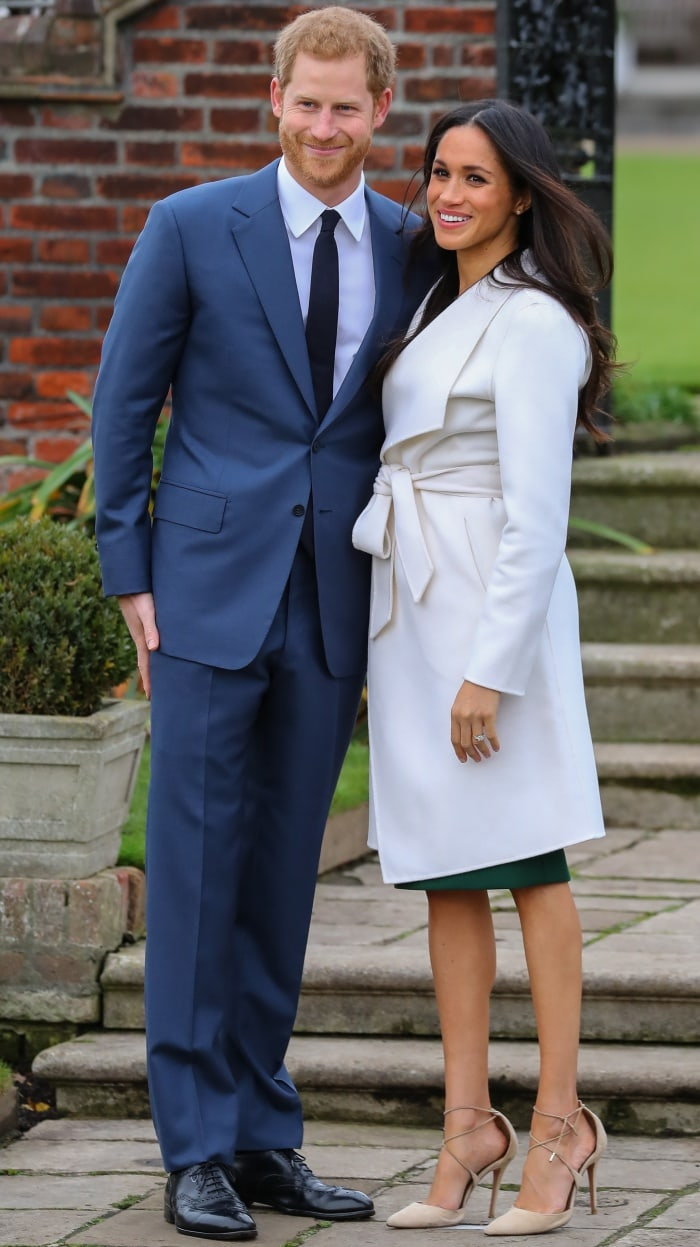 Prince Harry wearing a classic navy suit and Meghan Markle wearing a Line coat, P.A.R.O.S.H. dress, and Aquazzura heels