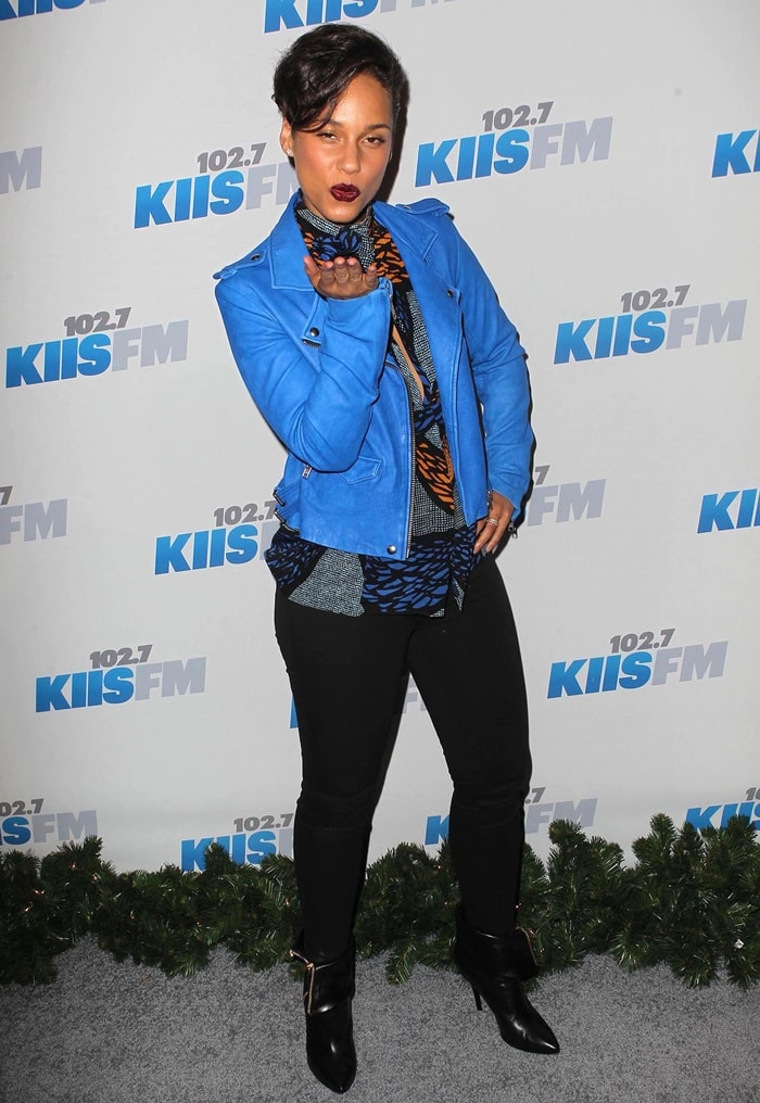 Alicia in a light-blue leather moto jacket, a printed top, black skinnies, and Giuseppe Zanotti fold-over zip ankle boots.