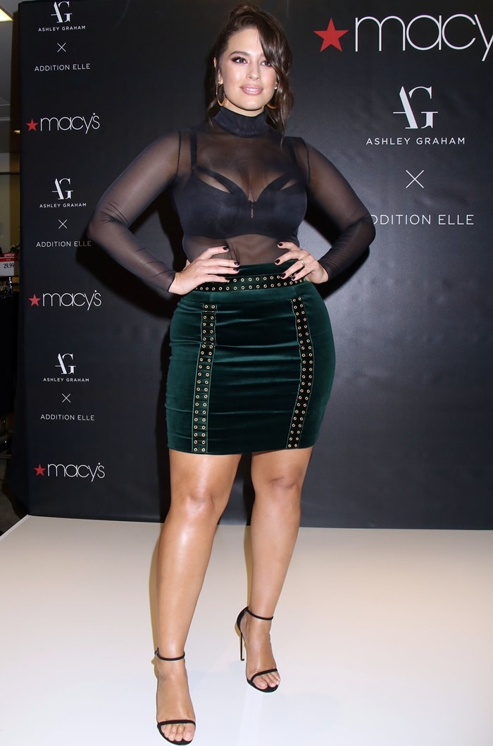 Model, Designer and Body-Positive Activist Ashley Graham showed off her curves in a sheer black long sleeve bodysuit paired with a bra from her collection and an incredibly tight skirt from Balmain