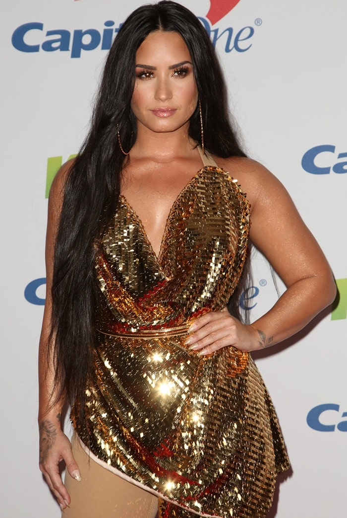 Demi Lovato'smonstrous Frolov Spring 2018 gold jumpsuit featuring one beige pant leg and an embellished counterpart