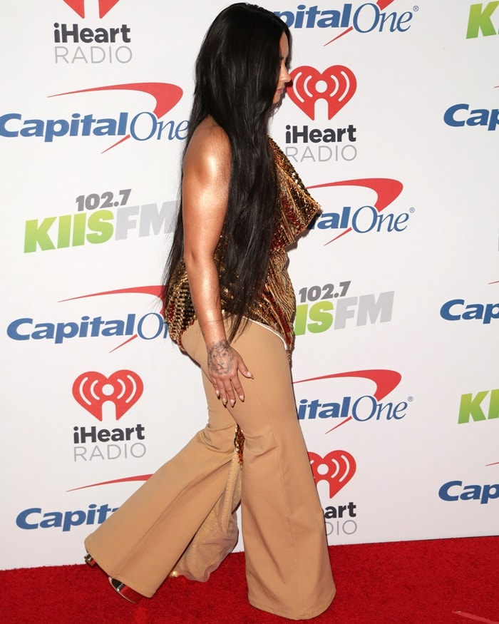 Demi Lovatocompleted her ensemble with big gold hoop earrings, a garish belt, and gold mirror leather 'Betty' platform sandals