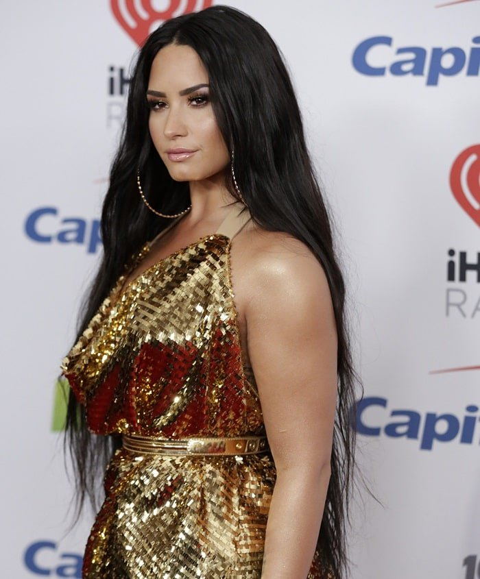 Demi Lovato'smakeup by Jill Powell was golden bronze while her long dark hair was parted down the middle