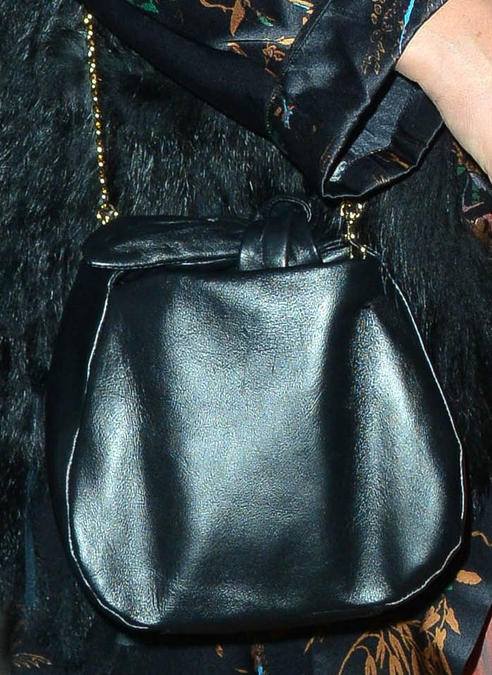 Jessica accessorized with a black leather bag with a knot on top