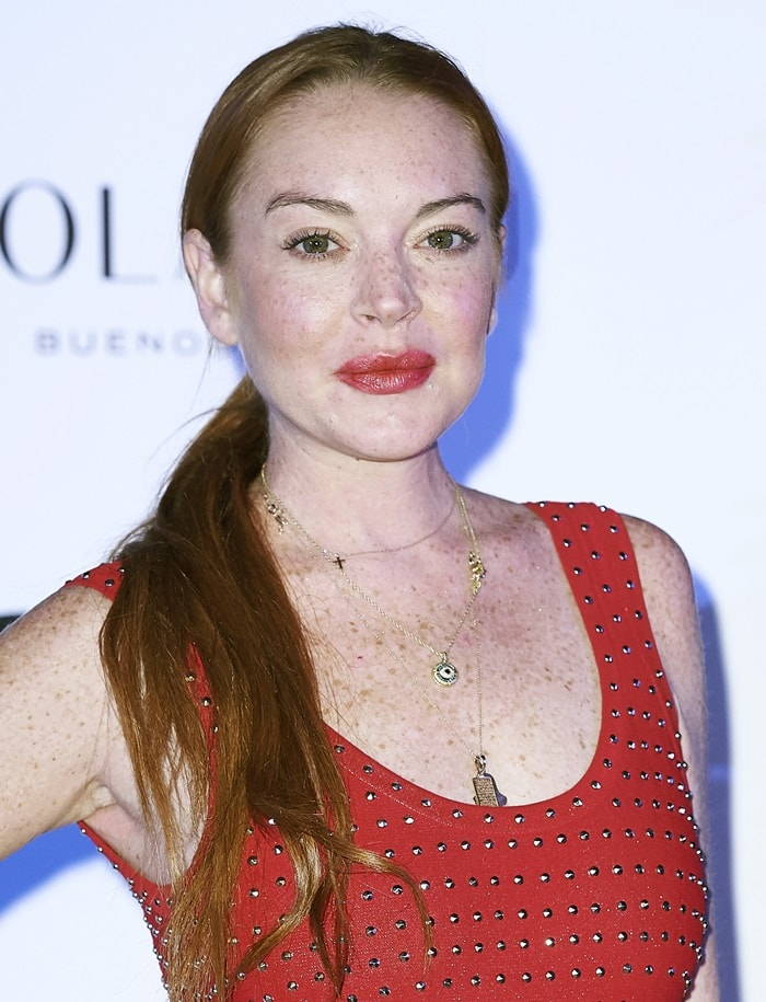 Lindsay Lohan showed off her cleavage in a studded crimson dress featuring a low-cut neckline