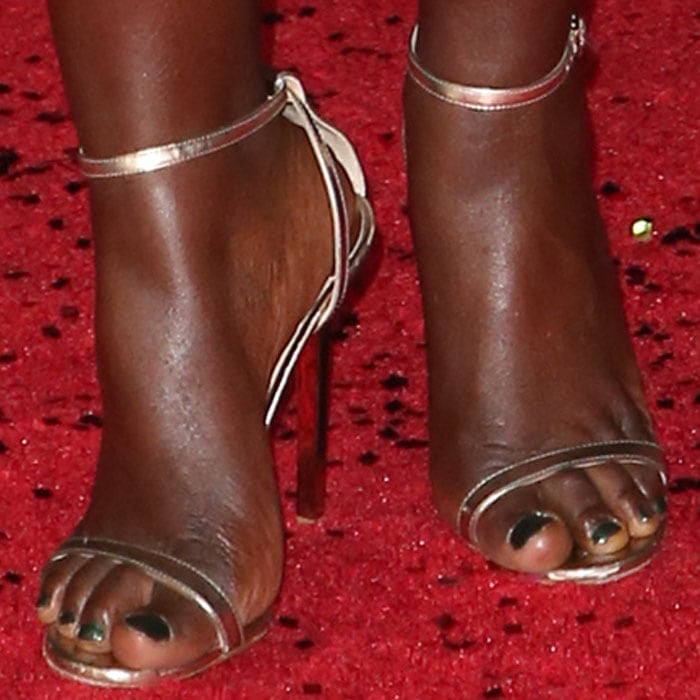 "Lupita brings the shine to her toes in a pair of Jimmy Choo ""Minny"" sandals"