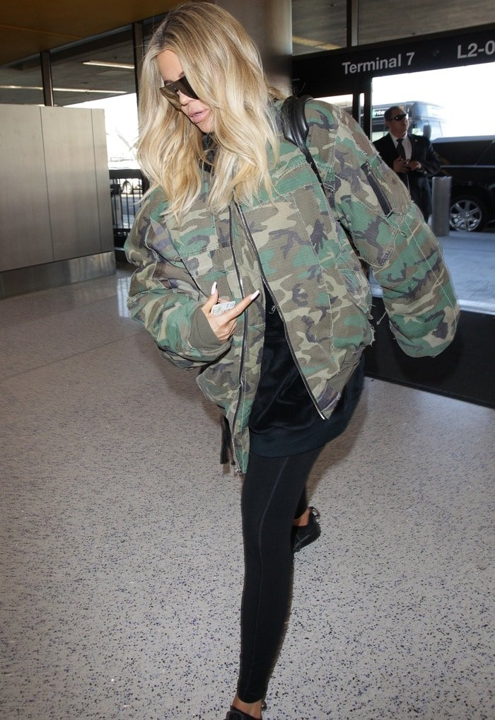 Khloe Kardashian styled her jacket with a black sweatshirt and leggings, oversized sunglasses, and a Louis Vuitton backpack