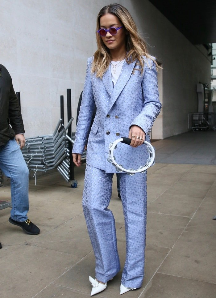 Rita Ora sported a polka dot suit from the Palomo Spain Spring 2018 collection and accessorized with purple Andy Wolf sunglasses and white pumps from Dior