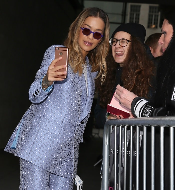 Rita Ora wearing a polka dot suit from the Palomo Spain Spring 2018 collection and carrying a tambourine as she arrives for an interview at BBC Radio 1 in London on December 4, 2017