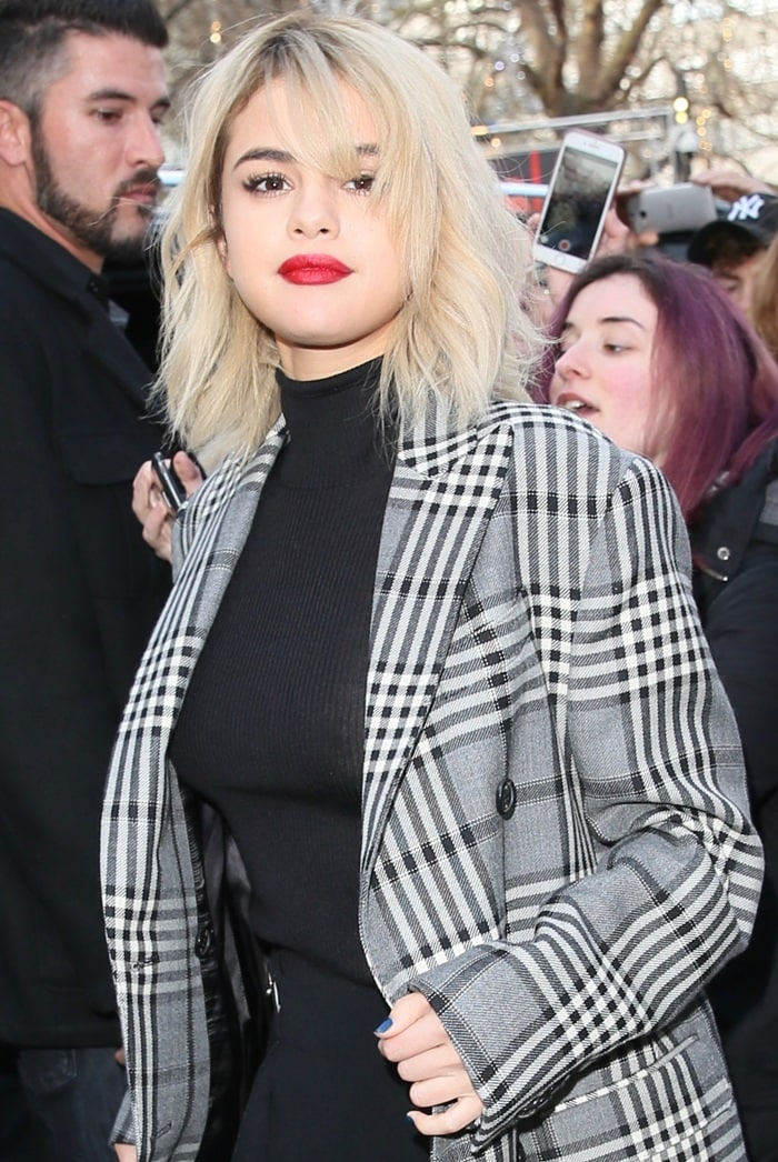 Selena Gomez wearing a double-breasted coat from Fay with tartan-print, flap pockets and upper breast pocket while arriving at the Global House in London on December 4, 2017