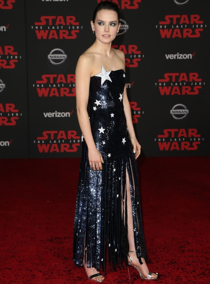 "Daisy Ridley wearing a Monse Spring 2018 gown and Christian Louboutin ""Jonatina"" metallic silver sandals at the ""Star Wars: The Last Jedi"" premiere"