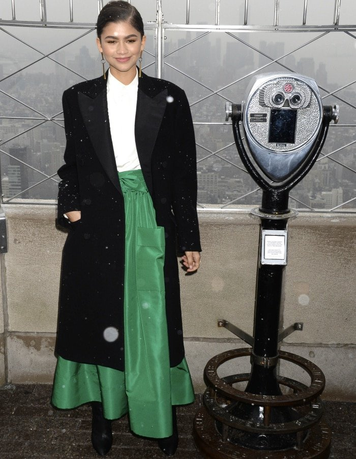 """Zendaya wearing a Ralph Lauren Fall 2017 coat, Martin Grant Spring 2018 skirt, and Giuseppe Zanotti """"Yvette"""" over-the-knee boots during a lighting ceremony atop the Empire State Building in New York City"""